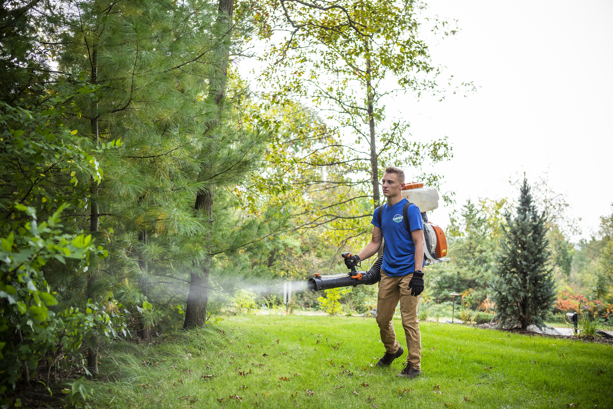 Mosquito control technician spraying residential property in Eau Claire, WI