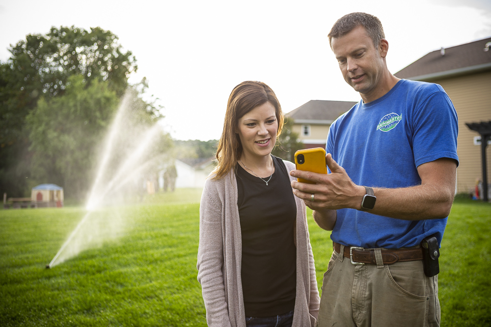 RainMaster irrigation technician and customer in lawn