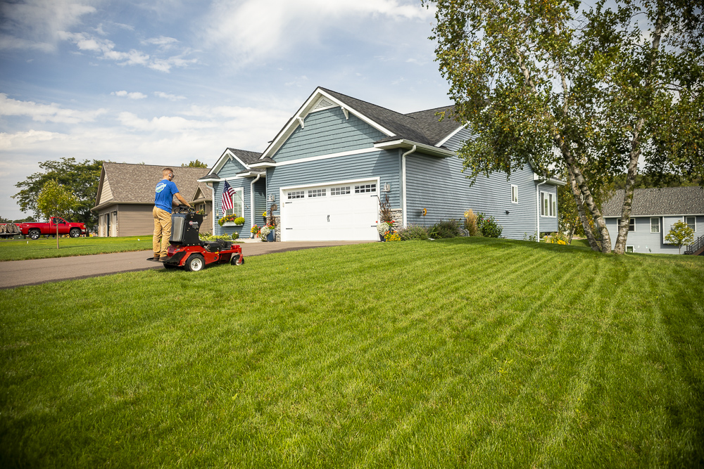 Lawn technician aerating lawn