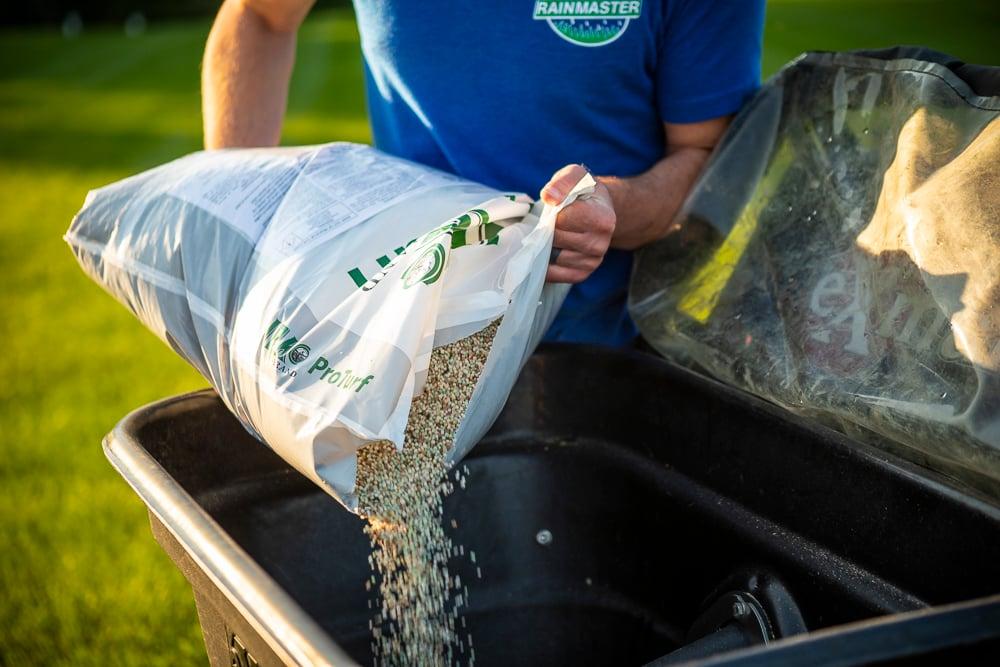 lawn team preparing fertilizer for a lawn