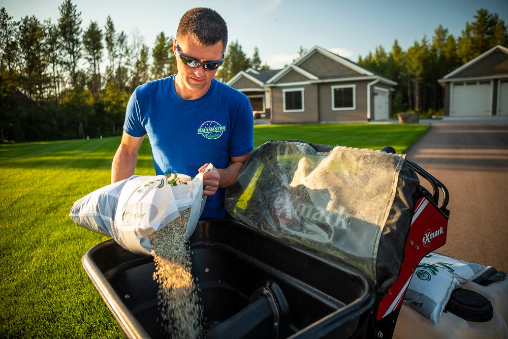 lawn professional applying fertilizer for lawn repair in WI and MN