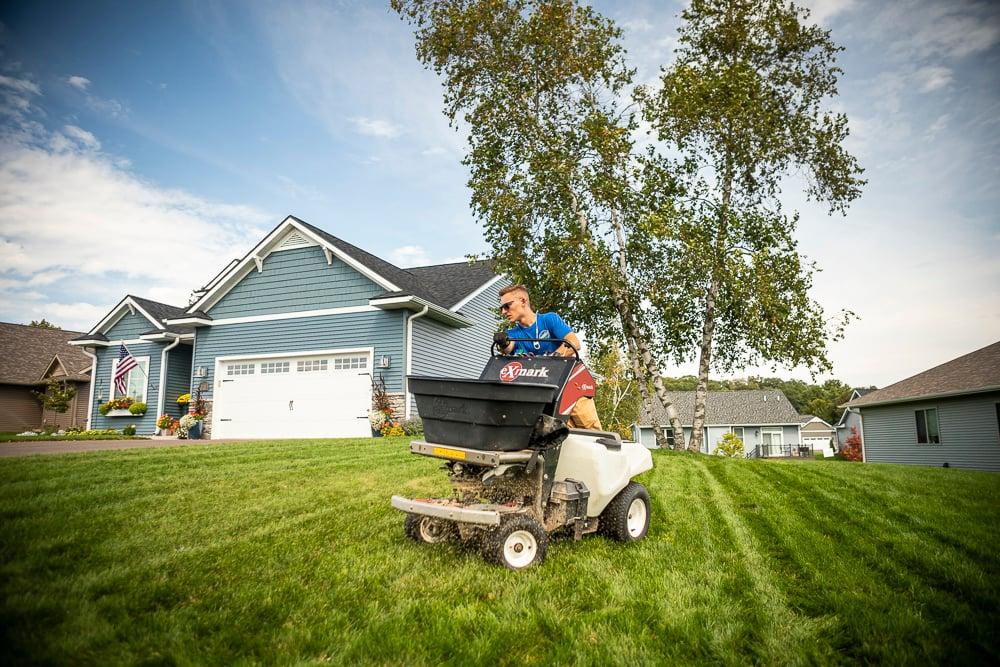 Lawn care technician in Minneapolis applying fertilizer