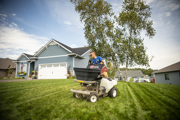 lawn care technician applying granular