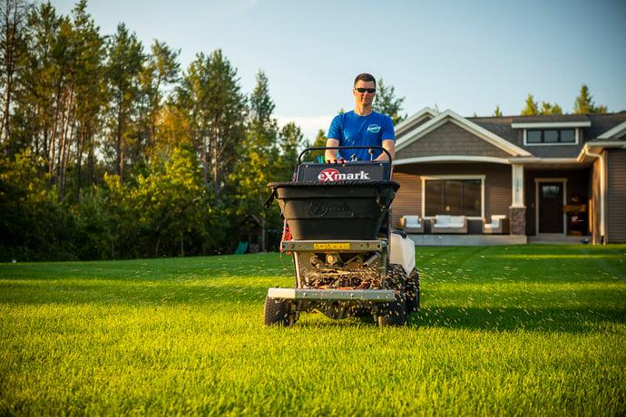 Lawn technician applying granular fertilizer
