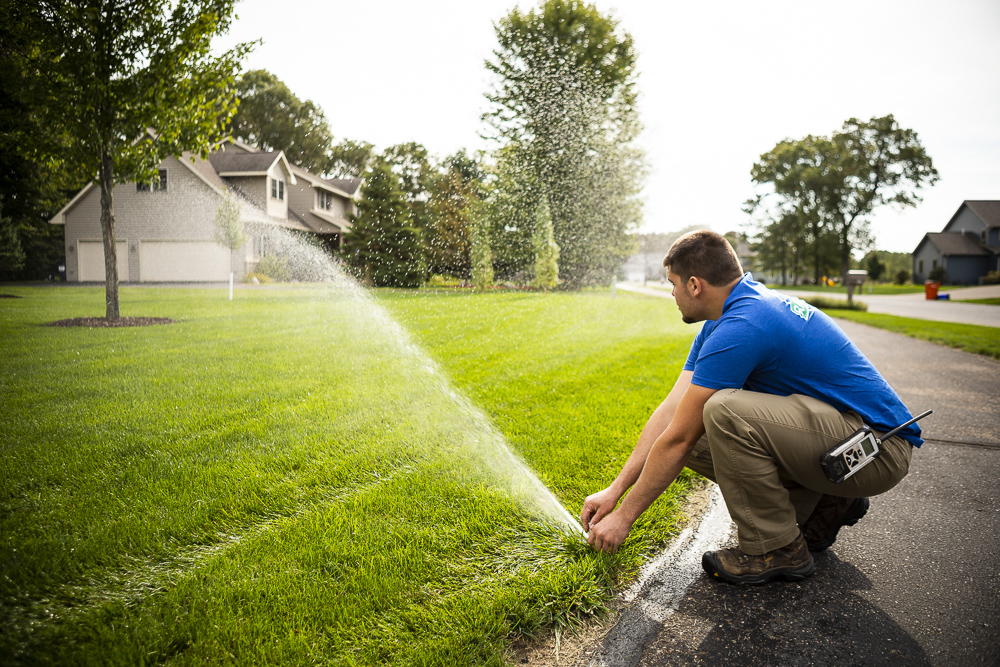 RainMaster irrigation technician adjusting sprinkler