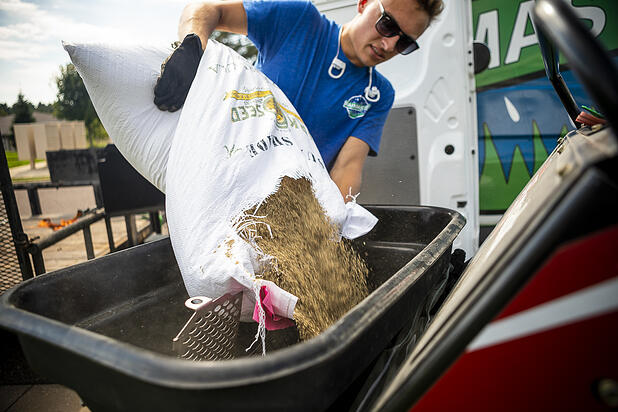 RainMaster lawn care technician pouring bag of grass seed
